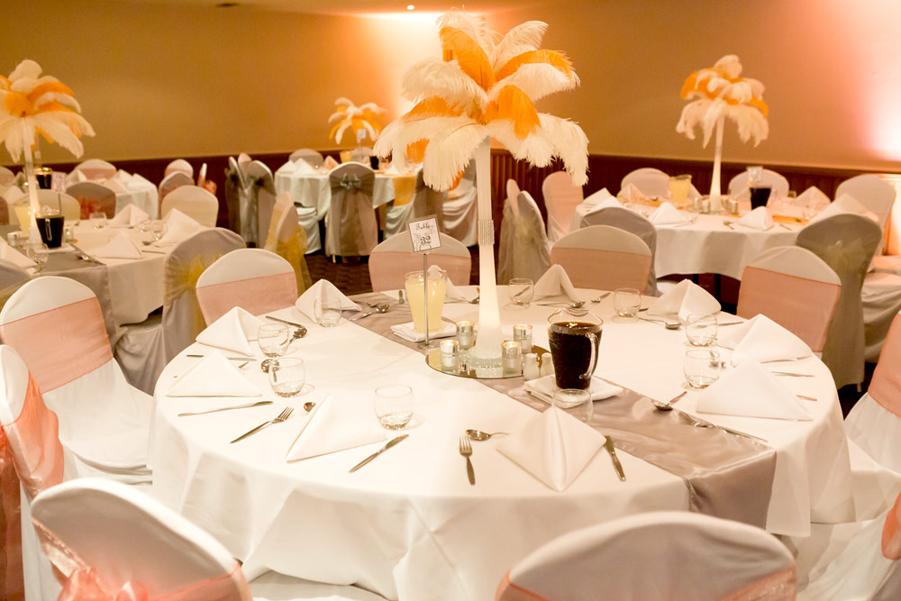 Wedding reception tables, chairs and feather plume features